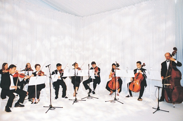 Violinists, cellists, and bassist perform at wedding ceremony