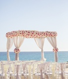 Wedding arbor on the beach destination wedding white rose pink rose fabric on back of chairs