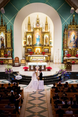 Wedding ceremony bride and groom at altar traditional wedding white chairs gold altar arch pews