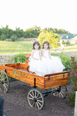 Two flower girls in white dresses inside wood wagon at Salamander Resort & Spa in Virginia