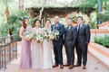 wedding portrait bride and groom two bridesmaids two groomsmen mismatched dresses bouquets courtyard