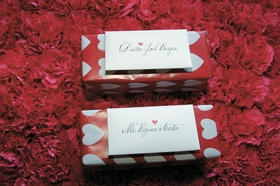 Escort cards attached to boxes with heart wrapping paper