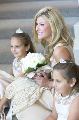 Bride sitting on steps with young guests