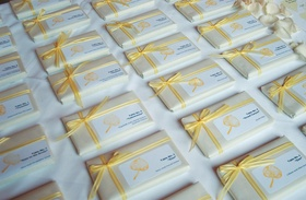 Small white box and escort card tied with yellow ribbon