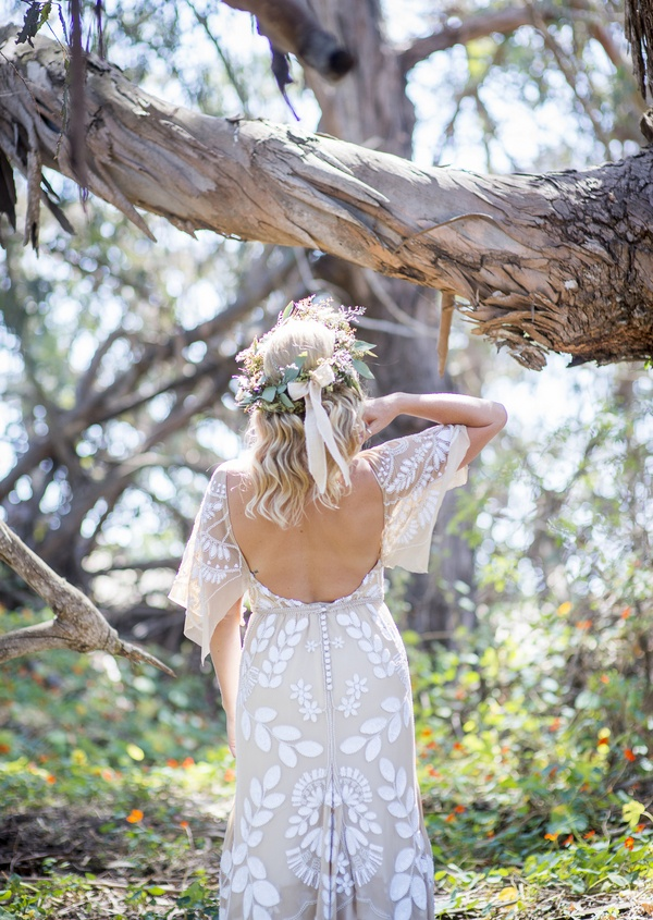 bohemian bride in detailed wedding dress with open back and head garland in santa barbara forest