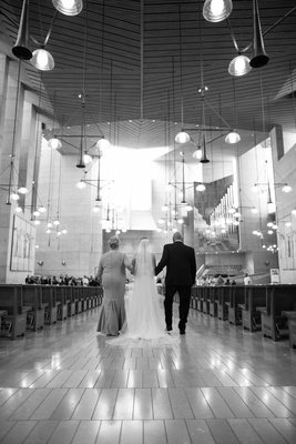 Black and white photo of parents walking bride down the aisle at Cathedral of Our Lady of the Angels