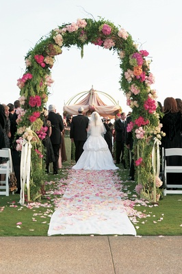 arch at beginning of aisle of greenery and pink flowers