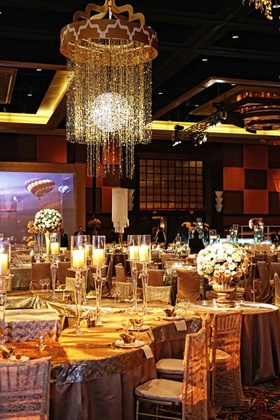 Wedding reception with tables covered in gold tablecloths and topped with tall candleholders