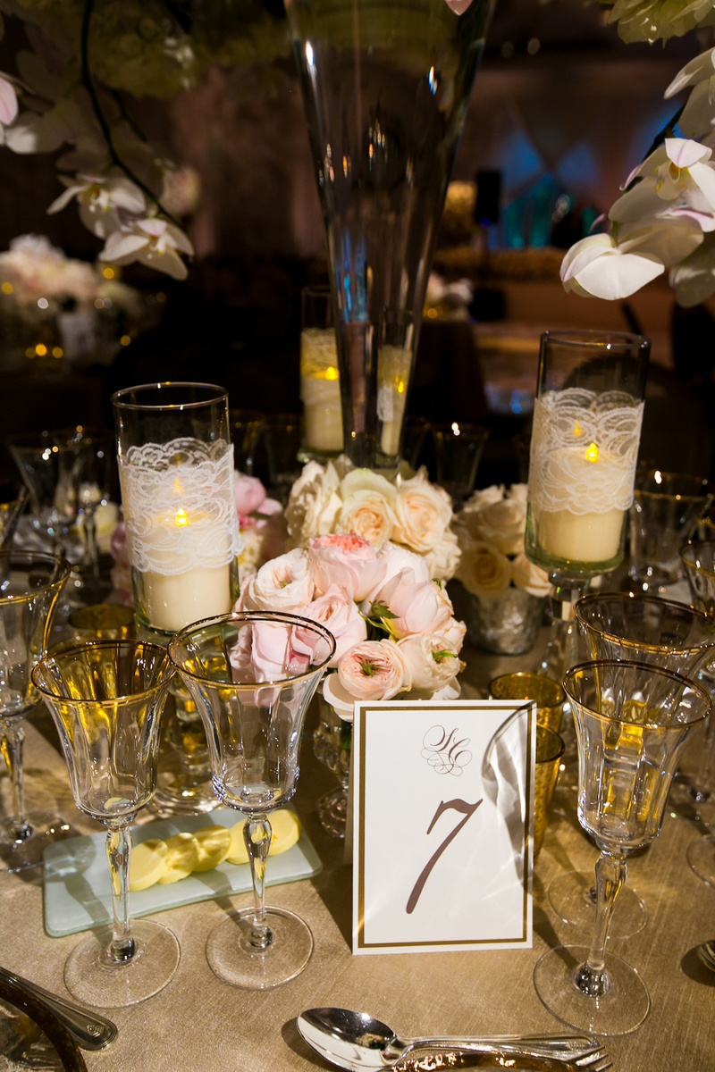 Gold and white table number at reception with pink garden roses