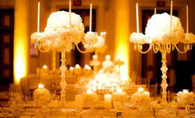 Table decor with crystal pedestals and tall candles and white flowers