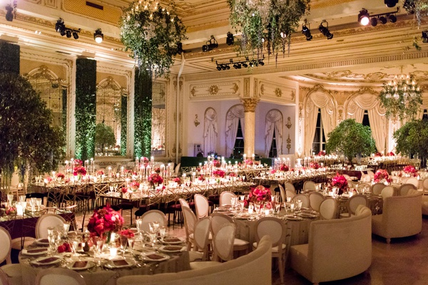 wedding reception ballroom hedge wall greenery chandelier round rectangle tables pink red flowers