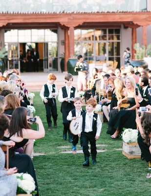 Four ring bearers in cowboy boots and bolo ties