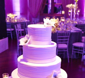 White cake with purple lighting and sugar flowers
