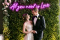 bride and groom in front of photo booth hedge wall neon pink purple all you need is love neon sign