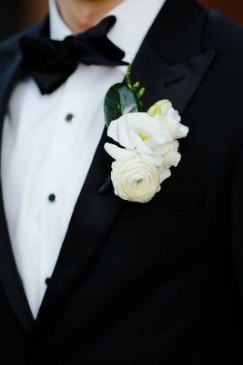 groom in tuxedo with multiple white flower boutonniere including ranunculus black bow tie green leaf