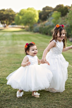 cute flower girls holding hands outdoor grass glitter shoes with bows ball gown pink orange roses