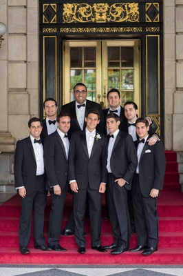 Groom and groomsmen in black tuxedos and bow ties in front of The Plaza