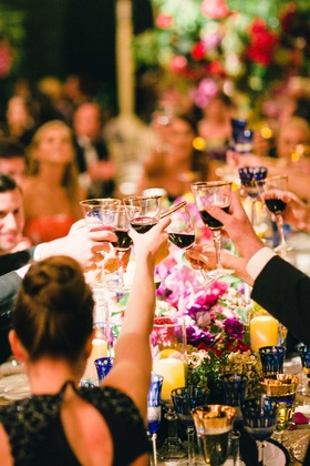 Wedding guests at tent wedding cheers and toast with gold rim wine goblets