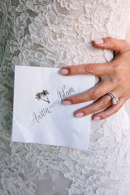 Bride in an Alencon lace dress, diamond rings, holds cocktail napkin with bride & groom's names