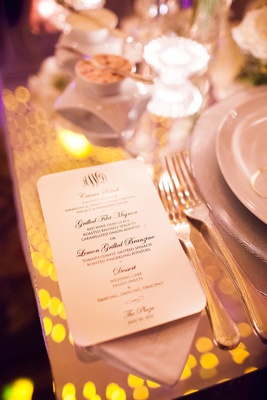 menu for wedding reception dinner on top of reflective clear table with reflection of lights