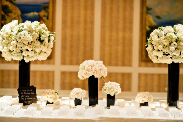 Escort card setting black vases white flowers white escort place cards