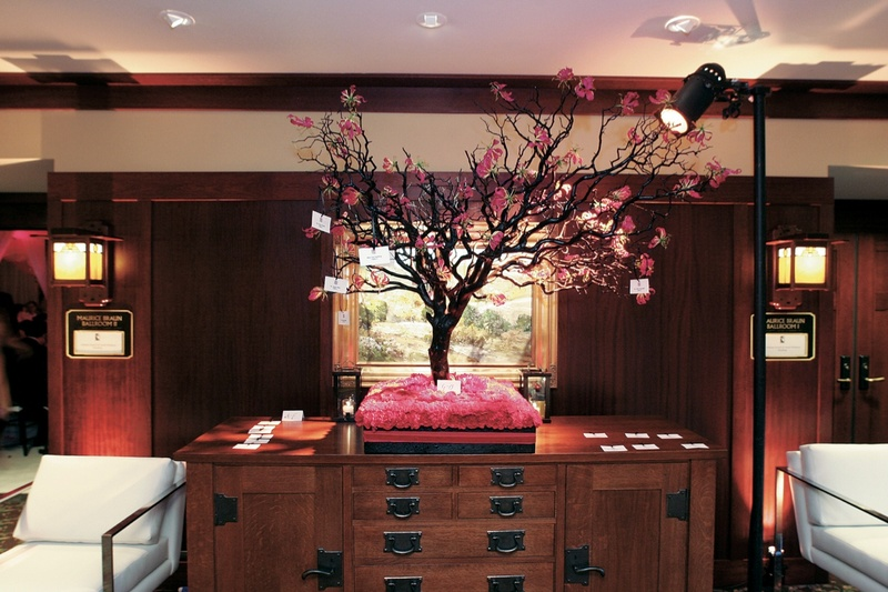 Pink cherry blossom tree on bed of flowers with place cards