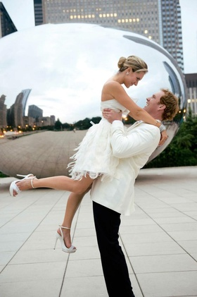 Bride in a short dress and groom in a tuxedo with a white coat and black pants