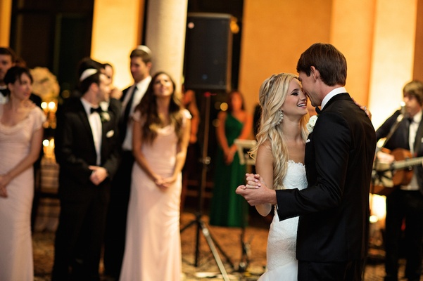 Bride in a strapless Romona Keveza gown dances with groom in a black tuxedo