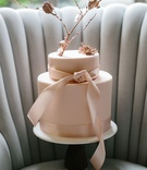 wedding cake on tufted settee chair channel tufts pink cake two layer rose gold branch and ribbon