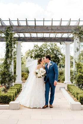 bride kissing groom veil blowing in wind groom in blue suit pink tie romona keveza wedding dress