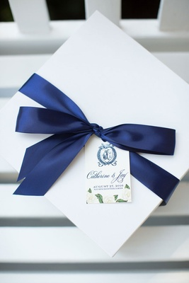 Tag on welcome box monogram, couple's names, wedding date, and hashtag with navy blue ribbon