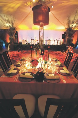 Tented reception area with modern fabric-wrapped chandeliers and dance floor with leaf projections