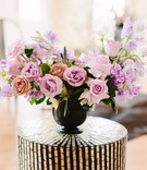 flower arrangement roses in shades of pink and lavender sweet peas, dark vase