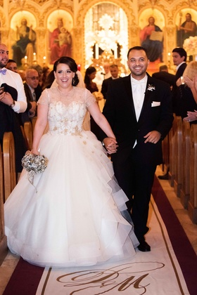 Bride in Lazaro wedding dress at ceremony aisle with custom Original Runner Company aisle runner