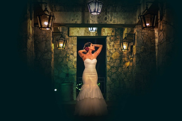 a bride in a trumpet white wedding dress poses in dark hallway with a bright red flower in her hair