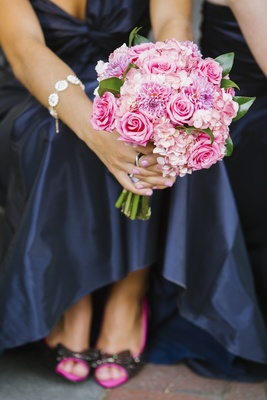 Bridesmaids holding bright flowers in ombre pattern