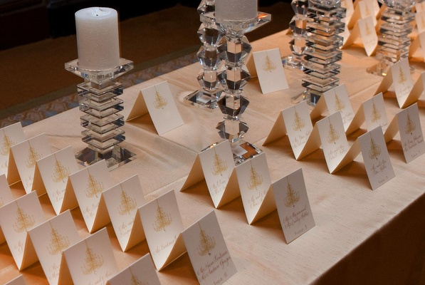 White seating card display with gold chandeliers