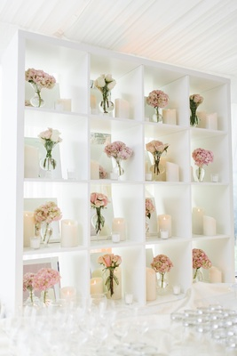 Bookcase behind wedding bar with pink clusters of flowers in bud vases and pillar candles
