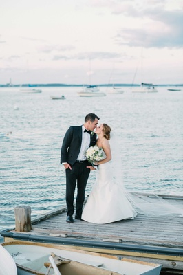 bride groom kiss on dock maine atlantic ocean cape elizabeth rivini green wedding color palette sea