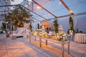 Cocktail hour room clear top tent trees on both sides of escort card table