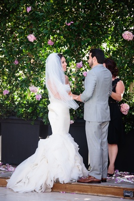 Bride in a fit-and-flare Vera Wang dress, ruffled skirt and groom in grey suit exchange vows