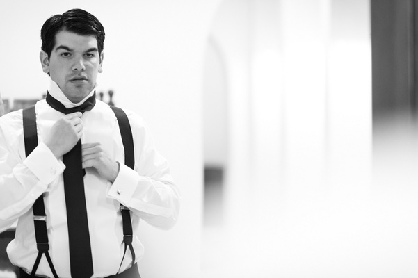 Black and white photo of man putting on tie