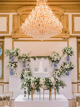 ballroom wedding reception sweetheart table greenery cake wall blue white vase and candlesticks