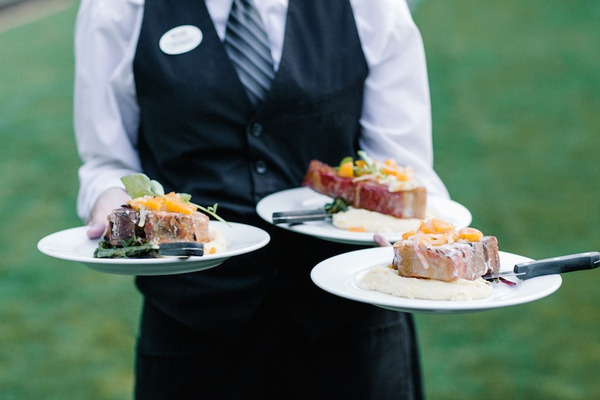 Wedding wait staff member with dinner plates of stuffed pork chops and salmon