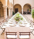 wedding reception historic abbey arch pillar courtyard long table patio chairs greenery lilac flower