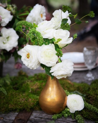 Outdoor wedding reception table with moss, a golden vase full of white flowers and greenery