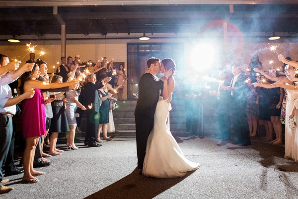 couple kiss with guests and sparklers