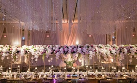 Wedding reception floating centerpiece over head table crystals on ceiling orbs candles