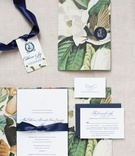 Wedding invitation suite with magnolia flower print navy blue ribbon and monogram nico and lala