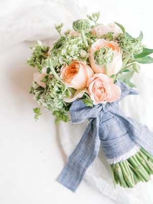 wedding event bridal shower bouquet peach roses greenery blue linen tied into bow around arrangement